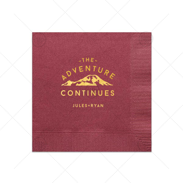The Adventure Continues Napkin | For the couple who loves getting outdoors add the perfect touch to your bar, dessert table or appetizers with this The Adventure Continues personalized napkin. Pair your names with the Shiny 18kt Gold mountain design for a seamless detail.